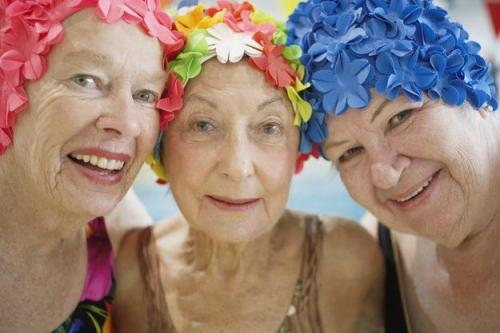 Older ladies in floral swimcaps smiling.